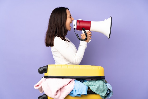 Woman holding megaphone over isolated wall