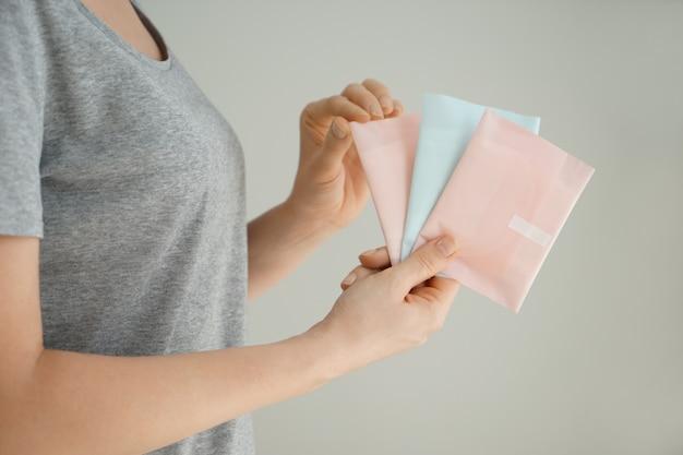Женщина, держащая менструальные прокладки на сером фоне