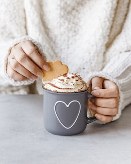 Woman holding metal grey mug of hot chocolate with whipped cream and cookie in hands.