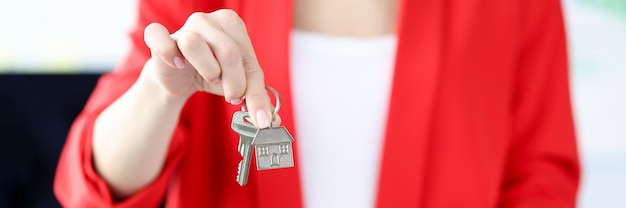 彼女の手でクリップボードに金属の鍵と文書を保持している女性クローズアップ不動産保険