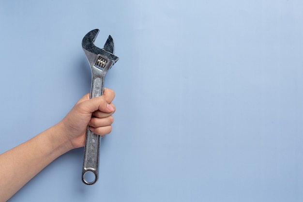 Woman holding metal wrench,labor day background concept
