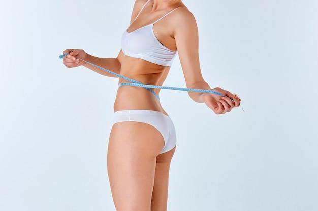 여자가 그녀의 아름 다운 몸의 완벽 한 형태를 측정하는 미터를 들고