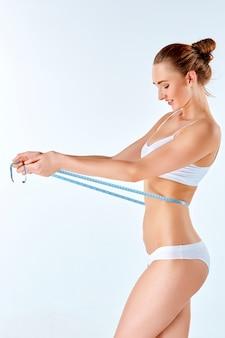 彼女の美しい体の完璧な形状を測定するメーターを保持している女性