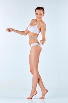 彼女の美しい体の完璧な形を測定するメーターを保持している女性