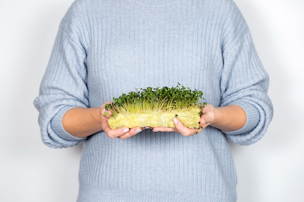 Woman holding micro greens, broccoli sprouts, five days old.