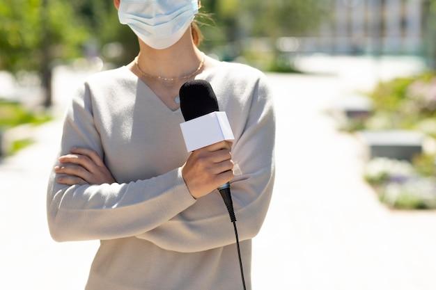 Donna che tiene un microfono mentre indossa una maschera medica