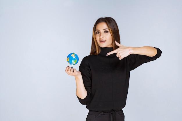 Donna in possesso di un mini globo e trovare posizioni su di esso.
