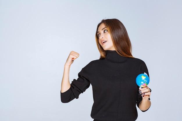 Donna che tiene un mini globo e mostra il pugno.