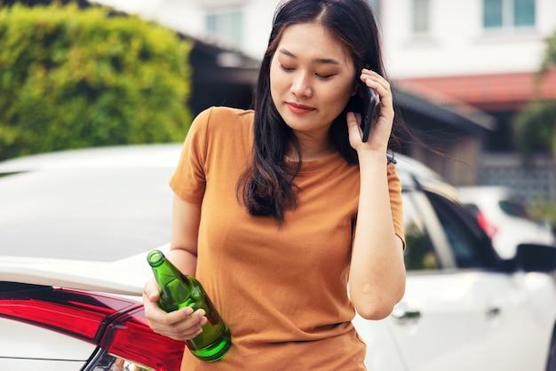 여자가 차에서 휴대 전화와 맥주 한 병을 들고. 마시지 말고 운전 개념