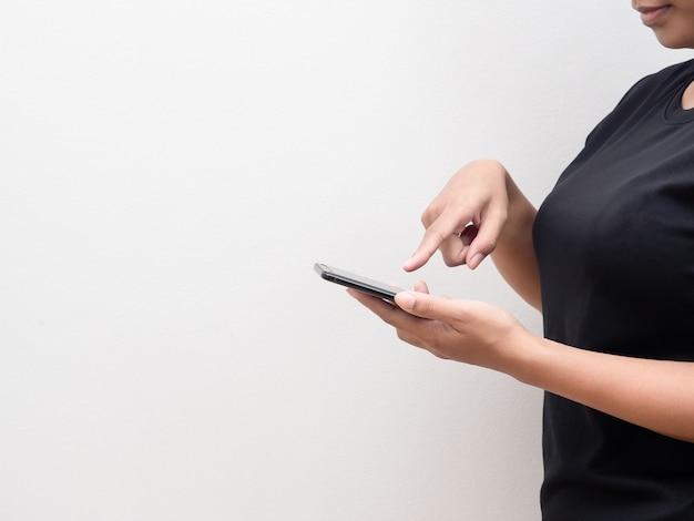 コピースペースの白い背景で買い物のための携帯電話とタッチスクリーンを保持している女性