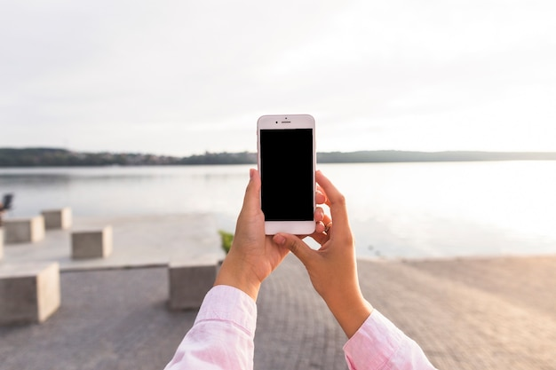 Woman holding mobile phone in front of idyllic lake