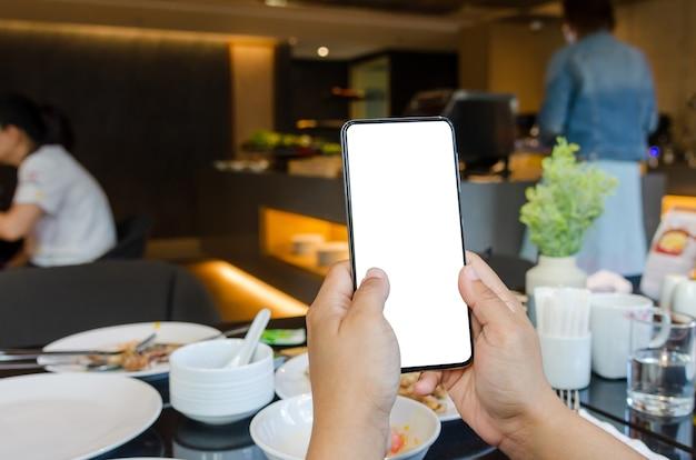 Женщина, держащая мобильный телефон в кафе