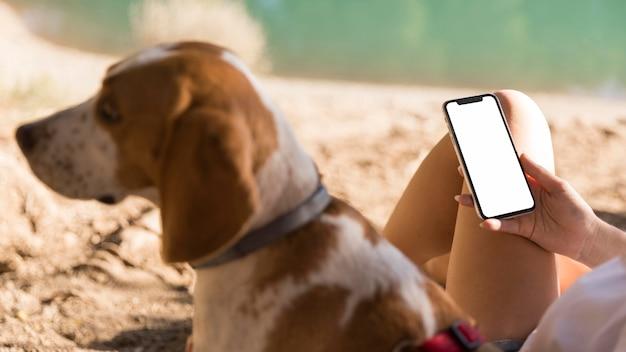 犬の横に携帯電話を持っている女性