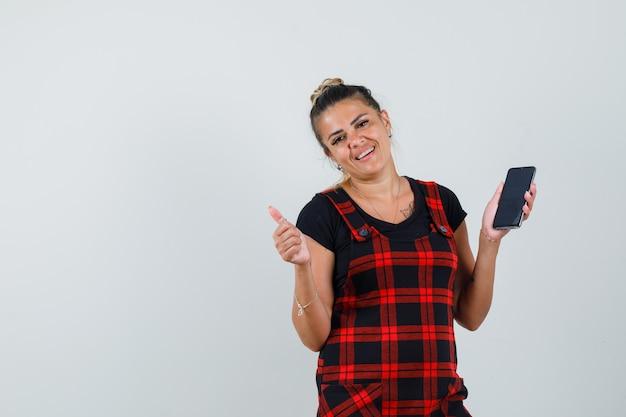 Женщина, держащая мобильный телефон, показывающая большой палец вверх в платье-сарафане и веселый вид. передний план.