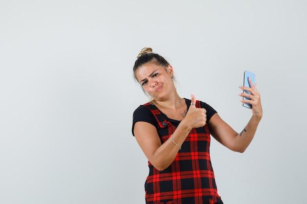 Женщина, держащая мобильный телефон, показывая большой палец вверх в платье-сарафане, вид спереди.