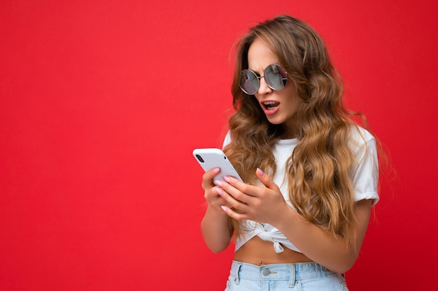 Woman holding mobile phone wearing sunglasses everyday stylish outfit isolated over wall background
