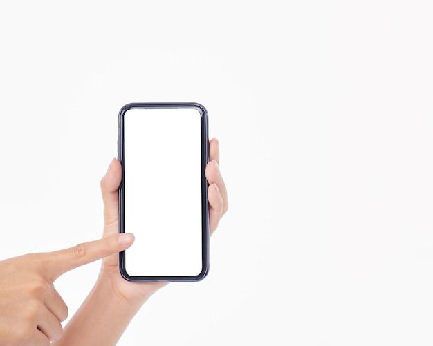 白い壁、クローズアップに空白の画面で携帯電話を保持している女性
