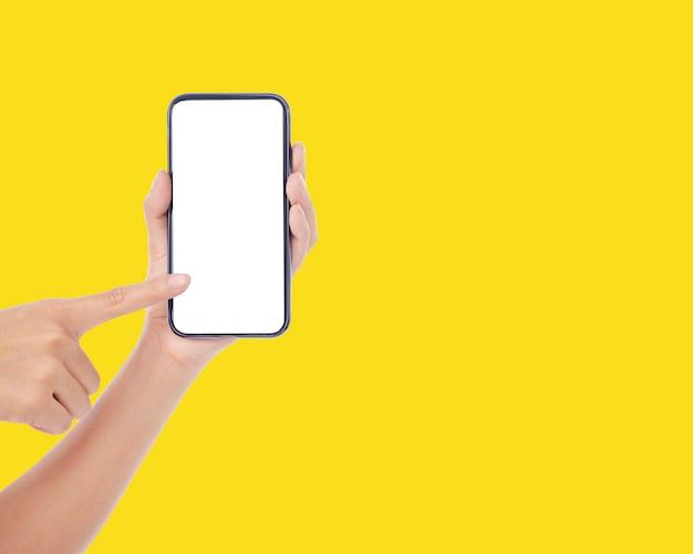 黄色の壁、クローズアップに空白の画面で携帯電話を保持している女性
