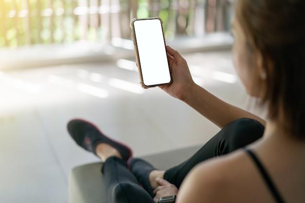 空白の白い画面で携帯電話を保持している女性。