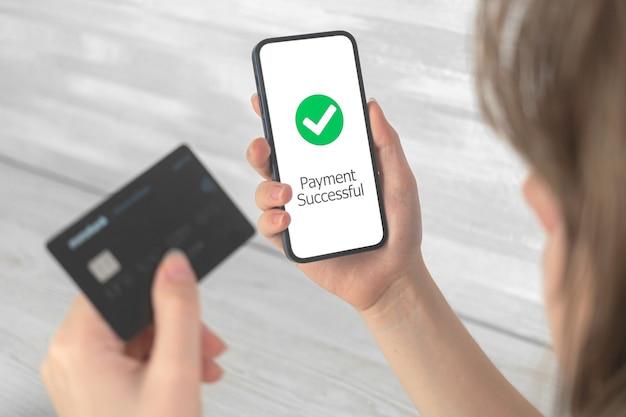 支払い成功画面とクレジットカードで携帯電話を持っている女性、インターネットでのオンライン注文または購入、銀行および転送技術のコンセプト写真