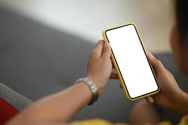 Женщина, держащая мобильный телефон с белым пустым экраном.