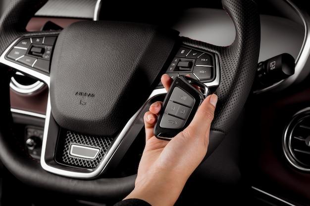 現代の車のキー、警報システム、電気ボタン付きステアリングホイールを保持している女性 Premium写真