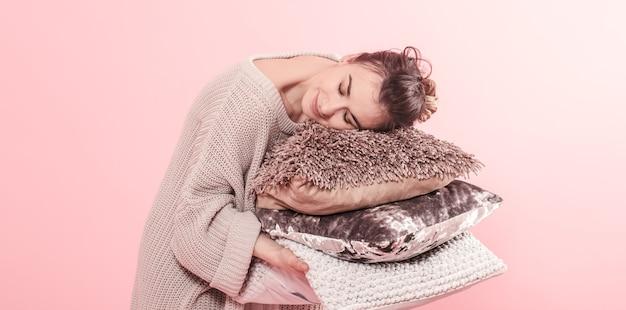 ソファ、トレンドのピンクの壁の背景、ミニマリズムのきれいな居心地の良いホームコンセプトのモダンな3つの枕を保持している女性。家のリビングルームの秋の装飾