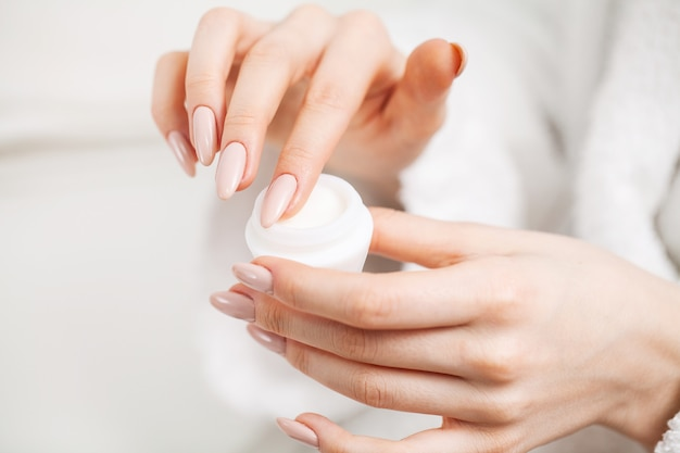 Woman holding moisturizer for skin care