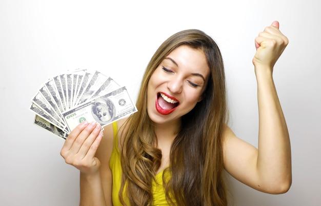 お金の紙幣を保持し、祝う女性
