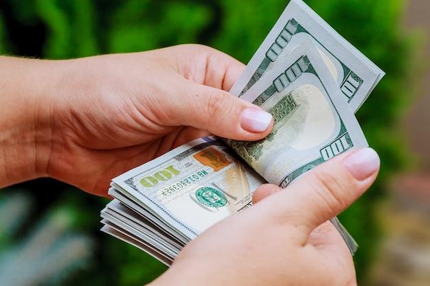 手にお金を持っている女性。ドル紙幣を数えます。