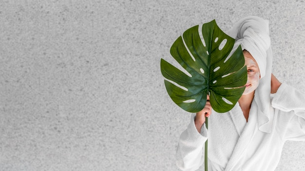 Woman holding monstera leaf with copy-space