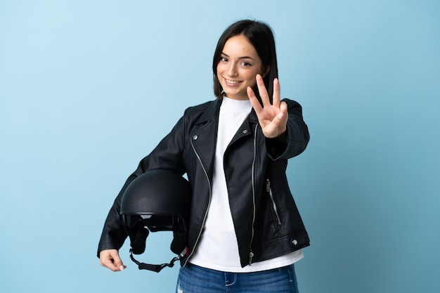 Woman holding a motorcycle helmet isolated on blue background happy and counting three with fingers