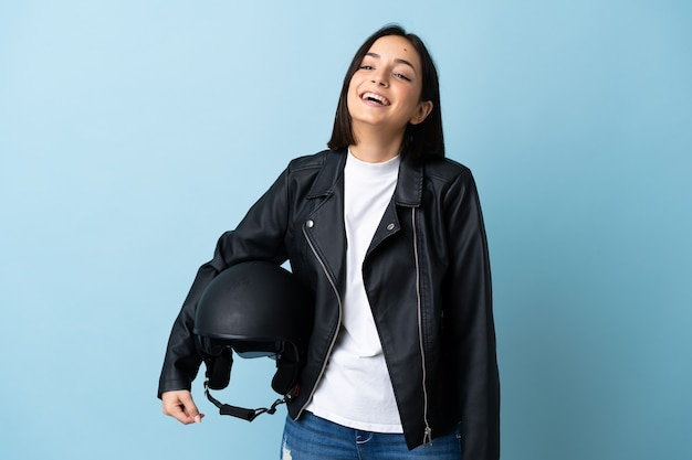 Woman holding a motorcycle helmet isolated on blue laughing
