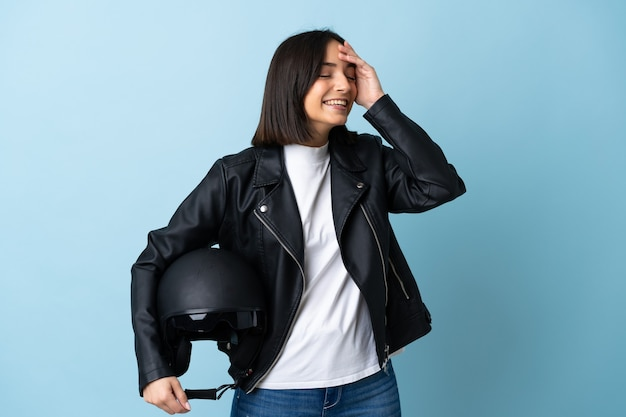 Woman holding a motorcycle helmet isolated on blue smiling a lot
