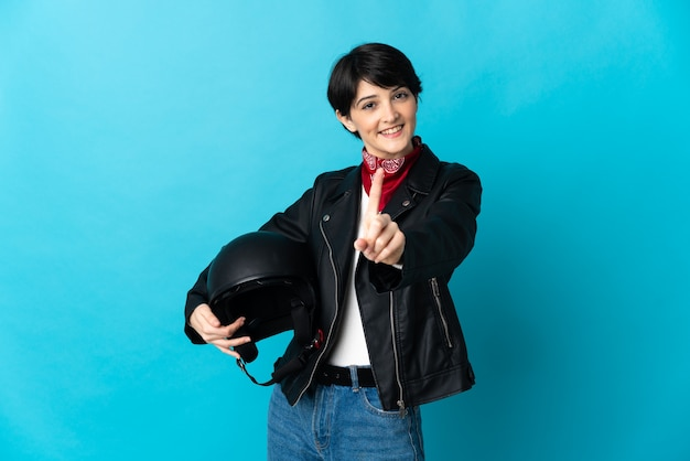 Woman holding a motorcycle helmet isolated on blue wall showing and lifting a finger