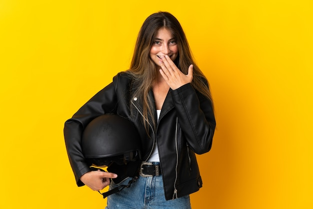 Woman holding a motorcycle helmet isolated on yellow happy and smiling coning mouth with hand