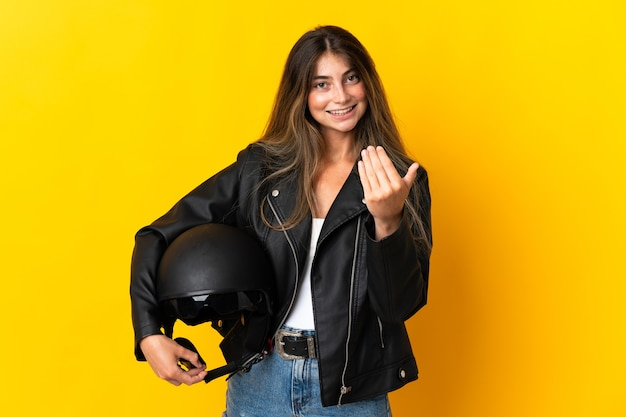 Woman holding a motorcycle helmet isolated on yellow inviting to come with hand. happy that you came