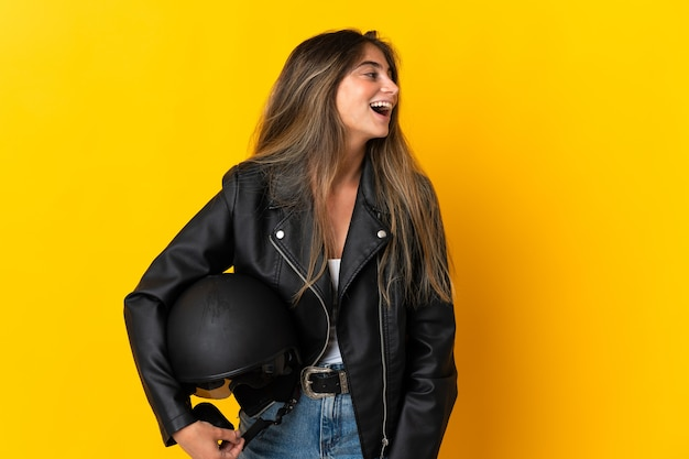 Woman holding a motorcycle helmet isolated on yellow laughing in lateral position