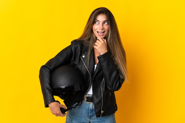 Woman holding a motorcycle helmet isolated on yellow looking to the side and smiling