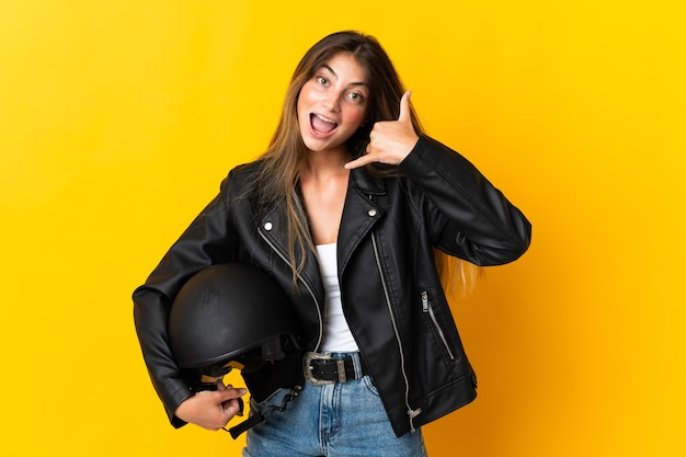 Woman holding a motorcycle helmet isolated on yellow making phone gesture. call me back sign