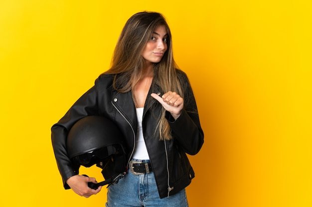 Woman holding a motorcycle helmet isolated on yellow proud and self-satisfied