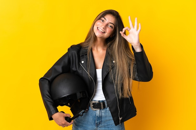 Woman holding a motorcycle helmet isolated on yellow showing ok sign with fingers
