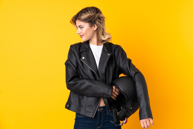 Woman holding a motorcycle helmet looking to the side