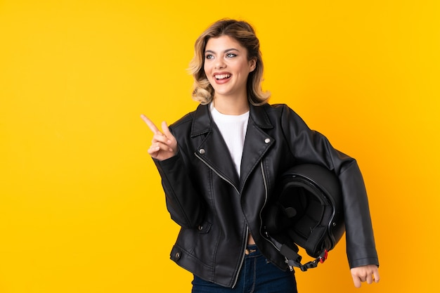 Woman holding a motorcycle helmet surprised and pointing finger to the side