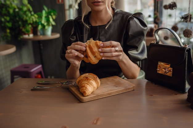 Woman holding a mug of coffee and a croissant in her hands in coffee shop. breakfast menu in the morning time.