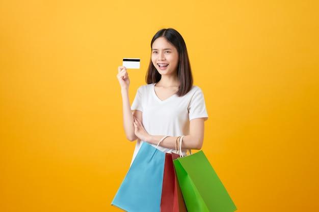 色とりどりの買い物袋とクレジットカードを持っている女性。