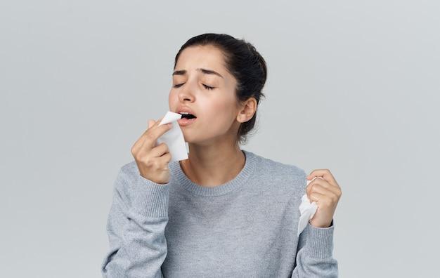 Женщина, держащая салфетку возле лица, проблемы со здоровьем, насморк, грипп. фото высокого качества