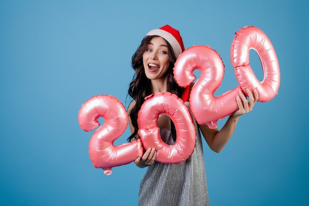Woman holding new year balloons wearing santa hat and dress