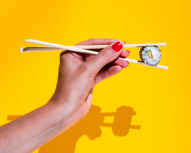 Woman holding a nigiri on a yellow background
