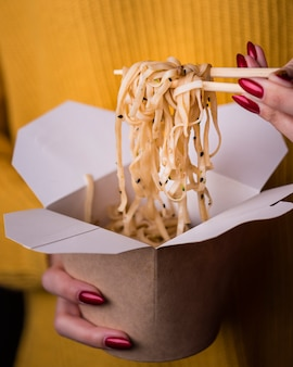 Woman holding noodles in chopsticks